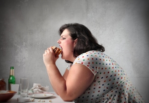 bigstock_Fat_woman_eating_a_hamburger_121636611