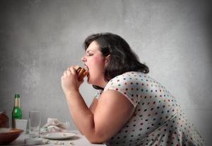 bigstock_Fat_woman_eating_a_hamburger_121636611